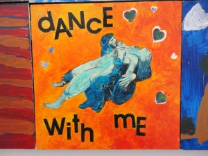 A photo of one panel of a community art project at the Ed Roberts Campus in Berkeley, California, depicting two figures dancing, one in a wheelchair. Artist Unknown. Photo by Cassandra Hartblay.