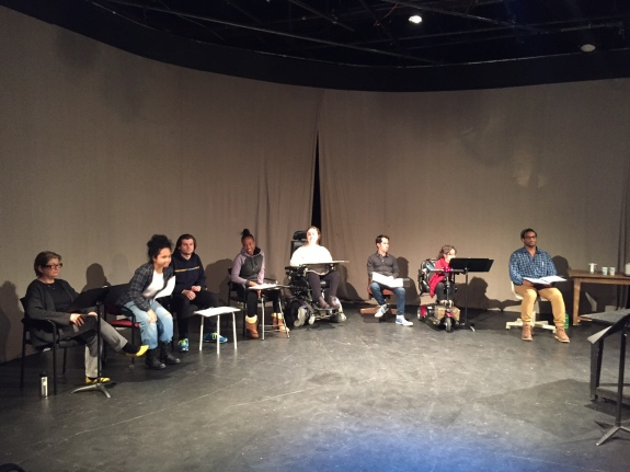The cast of the February 2016 staged reading of I WAS NEVER ALONE rehearses. Eight actors (young people of different genders and skin colors) are shown seated in front of a curtain, some on chairs or stools, others on their own mobility devices.