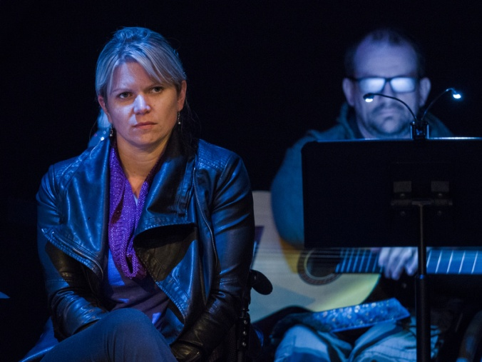 Regan Linton, a woman with blond center parted bangs, sits with legs crossed wearing a leather jacket and silver earrings, facing the camera, but lookign elsewhere. Behind her and to the right, out of focus, Vladimir Rudak sits behind a music stand illuminated by two small lights over the music. He holds a guitar in his lap, and his reading glasses are fogged or made otherwise opaque by blue-tinted stage light that washes across the image; the background of the photo is black. They are both seated, but only someone who saw other angleswould notice that they are both seated in wheelchairs because the wheels and handles hardly appear in the frame.