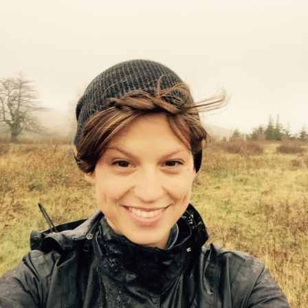 This image shows Cassandra, from the shoulders up. She is wearing a black raincoat and smiling. Her hair is blowing out from under a black cap. A rainy yellow-green landscape with small grey trees and white sky are in the background.