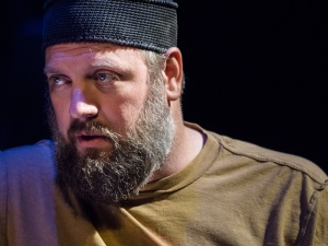 Production Photo by James Carmody of a Staged Workshop of I WAS NEVER ALONE at UCSD. Jason Dorwart as Rudak. Rudak wears a knitted black skull cap and a brown tshirt, and looks to the left, close up on his face with dramatic stage lighting.