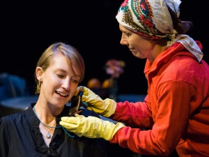 Production Photo by James Carmody. Molly Maslak as Anya and Judy Bauerlein as Larissa in a 2016 staged reading of I WAS NEVER ALONE. Anya talks on the phone, while Larissa, wearing a red sweatshirt, yellow cleaning gloves, and a kerchief over her hair holds the phone to Anya's ear.