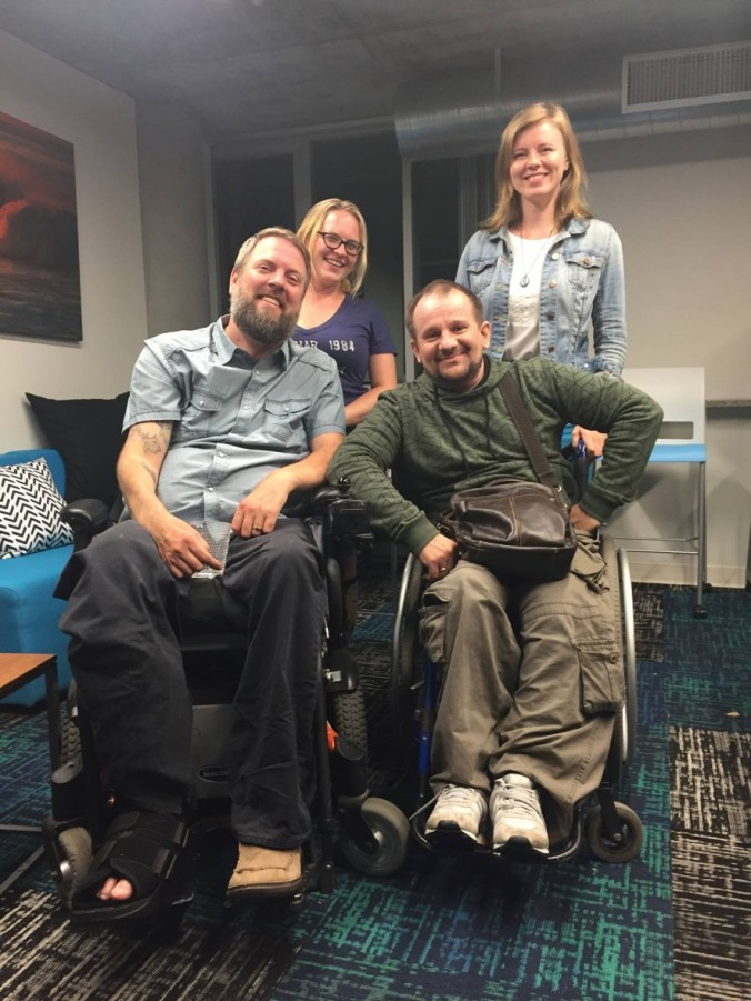 Jason is a young white man with a grey beard. He is wearing a blue short sleeve buttondown shirt, smiling, and sitting in a power wheelchair. Behind him is Laura Dorwart, who has medium length blond hair and glasses and is wearing a dark blue tshirt and smiling. Vladimir Rudak is a white man in middle age. He is wearing a dark green hoodie, and sitting in a manual wheelchair next to Jason. Rudak is smiling and leaning toward Jason and has is elbow on Jason's chair's arm rest. Standing behind Rudak is Larisa, a tall woman with blond hair wearing a light blue jean jacket with a white shirt and necklace, and smiling at the camera.