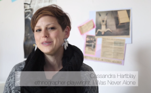 Cassandra Hartbaly sits in front of a white wall with newspaper clippings of theater articles on it, in even natural light. She is a white woman with short reddish brown hair and brown eyes, wearing chunky white earings and a big black scarf. She is looking at the camera and talking. A video title on the lower part of the image reads Cassandra Hartblay, ethnographer-plawright, I Was Never Alone.