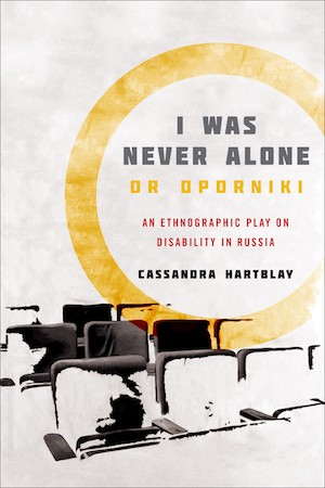 """book cover shows book title """"I was never alone or oporniki: an ethnographic play on disability in Russia: Cassandra Hartblay"""" in grey, yellow, and red text inside of a yellow circle reminiscent of a spotlight on an off-white background over a partial view of theatre seats which are painted in a way that some are fading into the background."""