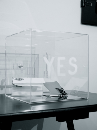"""installation view black and white photograph: a clear ballot box with the word """"YES"""" on the front sits on a table with several ballots inside of it."""
