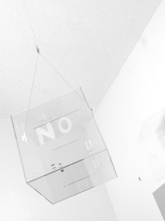 """Installation view black and white photograph: a clear ballot box with the word """"NO"""" on the front hangs from a wire from a high ceiling; it is empty, with no ballot inside."""