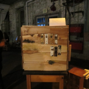 A wooden box with undiscernable gadgets affixed to it sits on a pedestal in an industrial space.